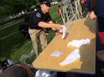 Volunteer police officer soaking cold towels for us runners.